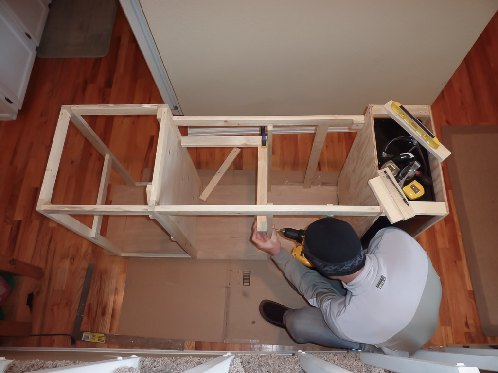 Working on cabinet framing inside on a freezing winter day.