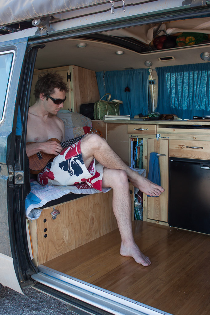 Tim playing Lili (our ukulele) in the van on the beach.