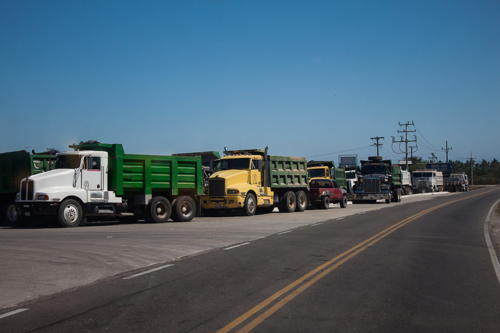 Trucks waiting to be loaded with chilies and tomatoes.