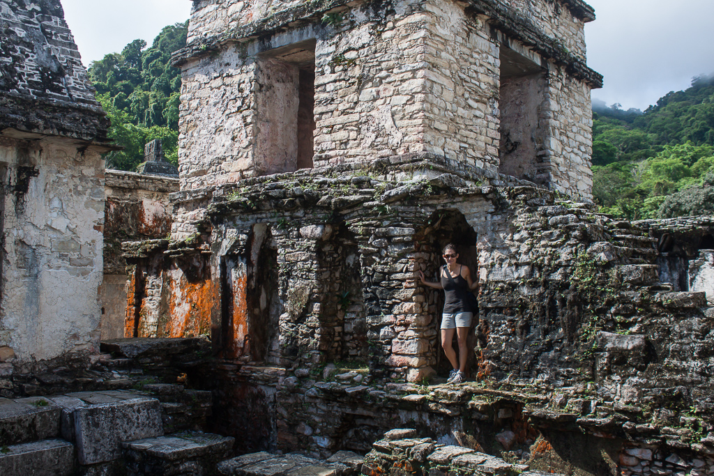 Emily peaking out of doorway of the central palance at Palenque.