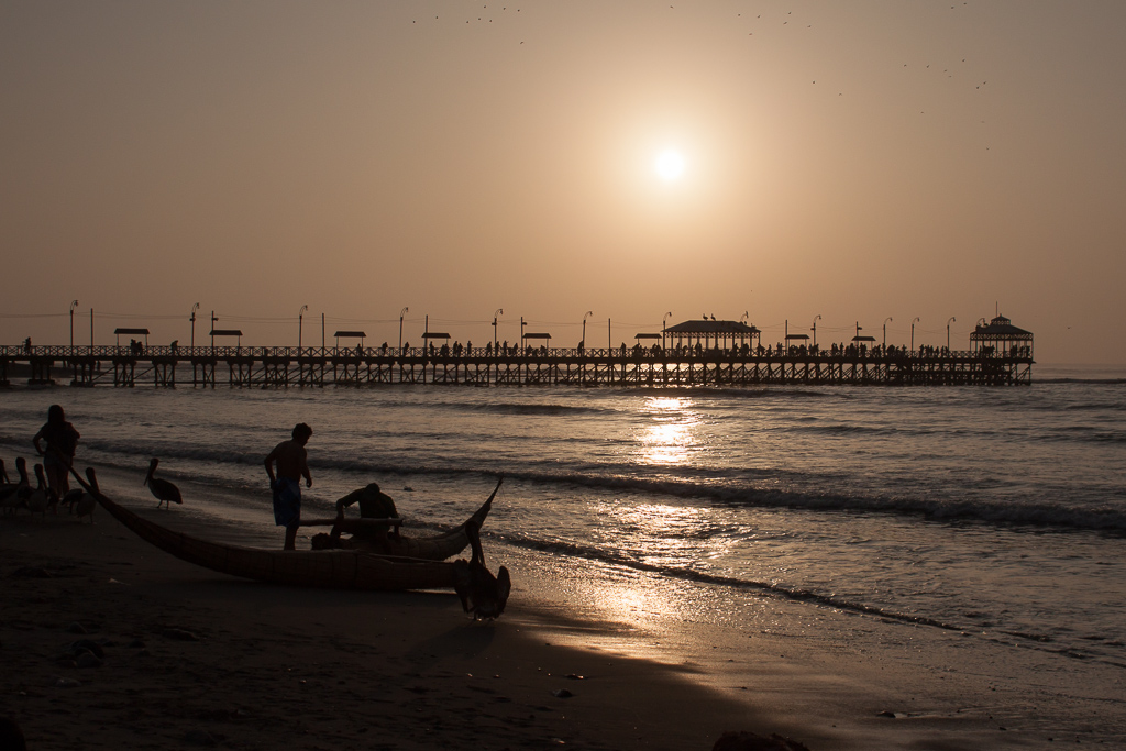 A fisherman with his traditional reed boat at sunset, Huanchaco.
