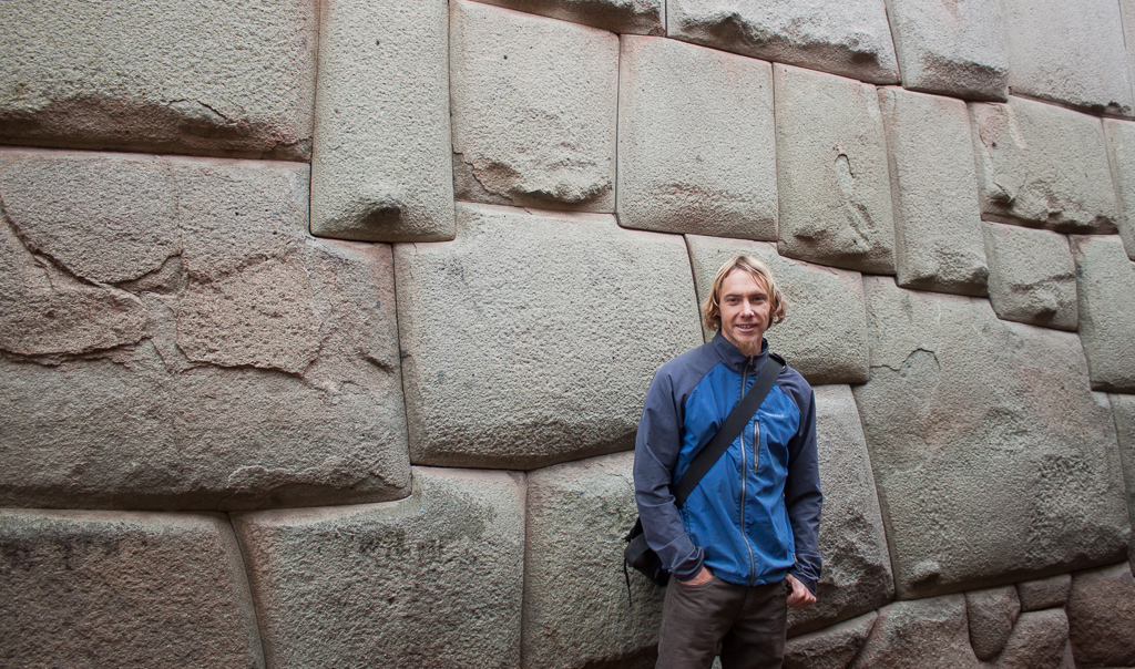 Tim posing in front of some Incan stonework that has been integrated into a modern building.